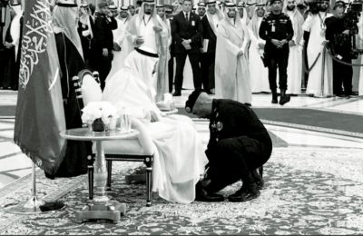 Maj. Gen. Abdulaziz Al-Fagham tying the shoe of King Salman.